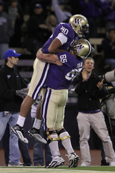 Kavario Middleton is hoisted up by Ryan Tolar after scoring a touchdown to continue the Husky comeback.