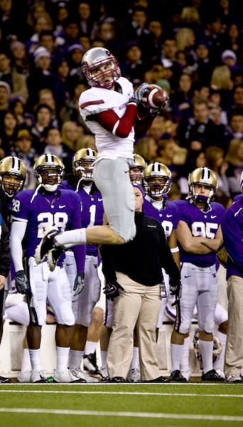 Cougar WR Gino Simone skies for a catch in front of the Husky bench.