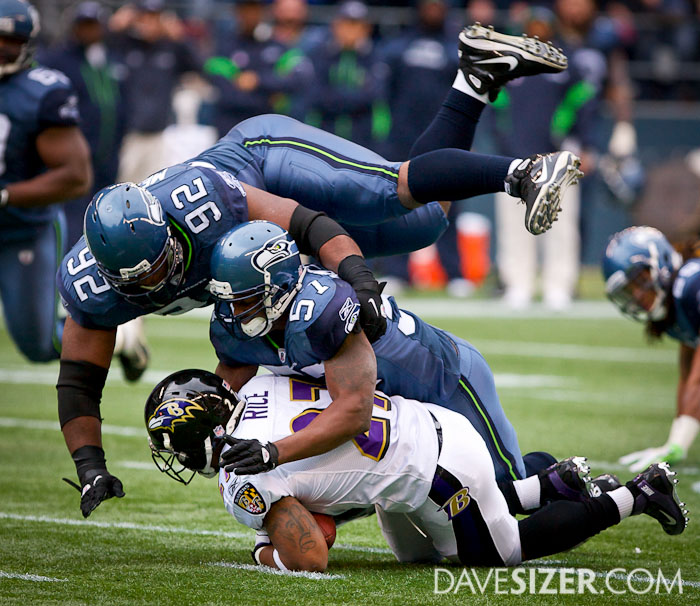 Brandon Mebane flies over David Hawthorne who wrapped up Ray Rice.