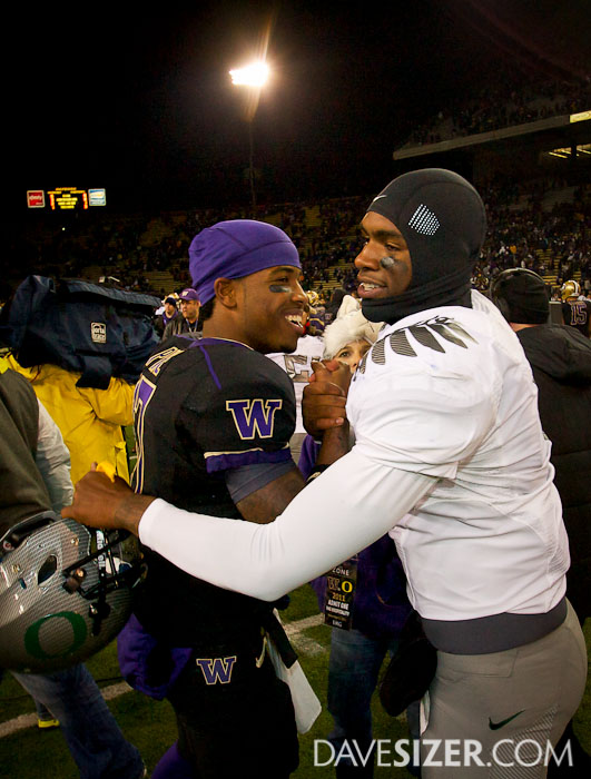 Keith Price and Darron Thomas hug after the game.