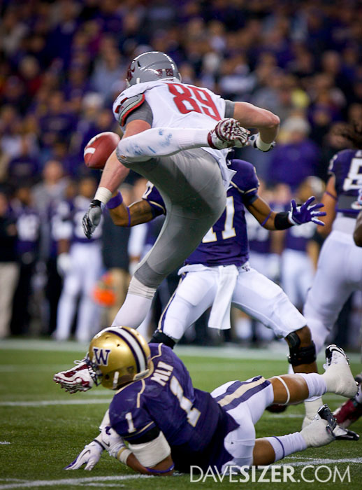 WSU's Travis Long leaps over Chris Polk trying to get to Keith Price.