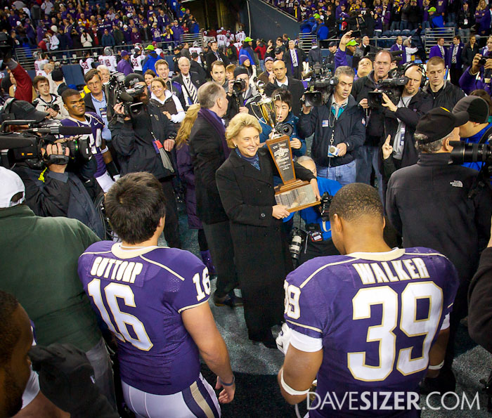 Washington Governor Christine Gregoire holds the Apple Cup trophy to present to the Huskies.