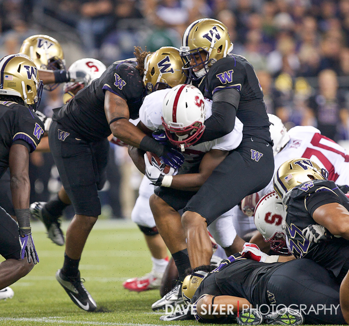 Stanford's Stepfan Taylor gets swarmed by two Huskies.