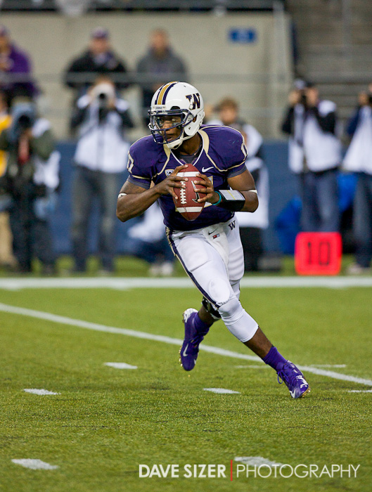 Huskies QB Keith Price rolls out looking for a receiver.