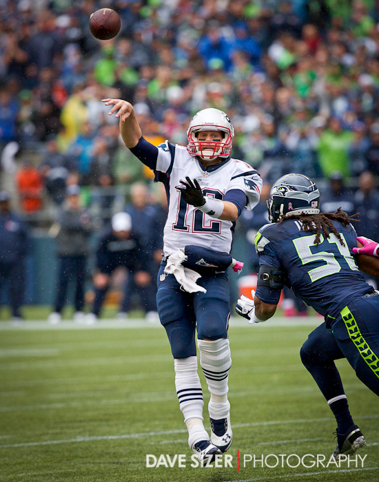 Tom Brady leaps to get a pass off over Bruce Irvin.