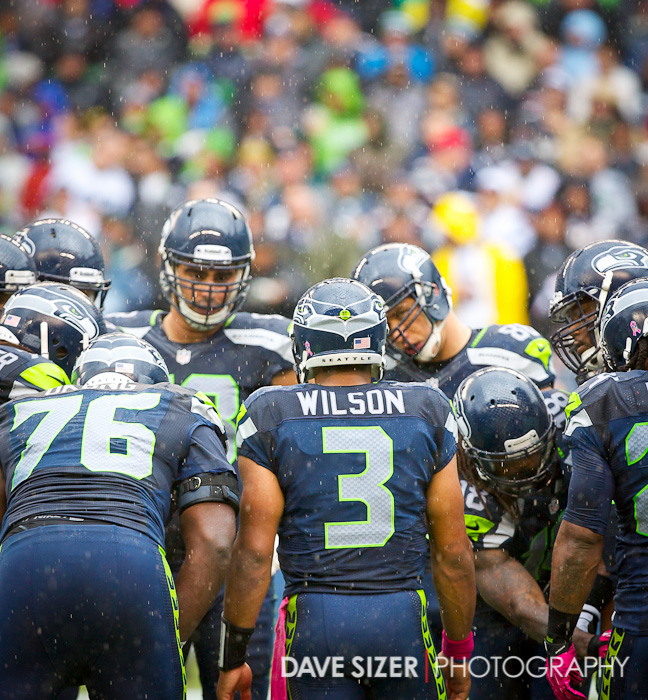 Russell Wilson huddles the team up as the rain continues to fall.