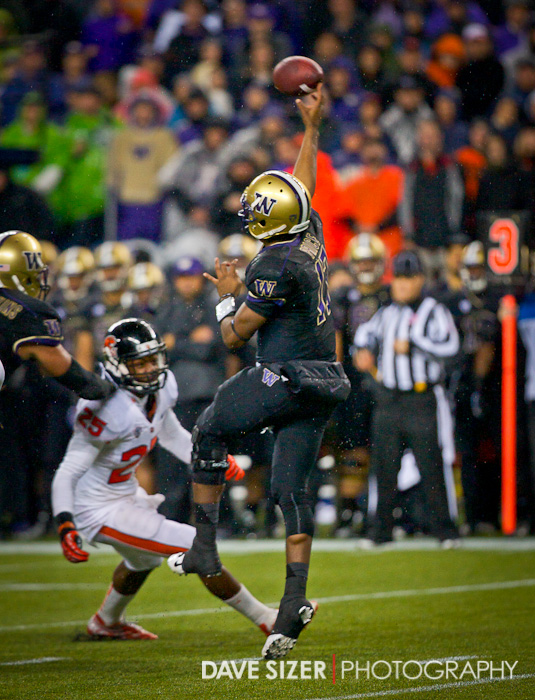 Washington's Keith Price leaps as throws over the OSU defenders.