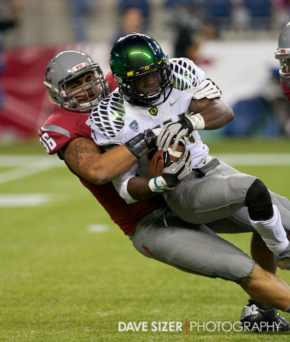Oregon's Kenjon Barner gets brought down by WSU's Xaiver Cooper.