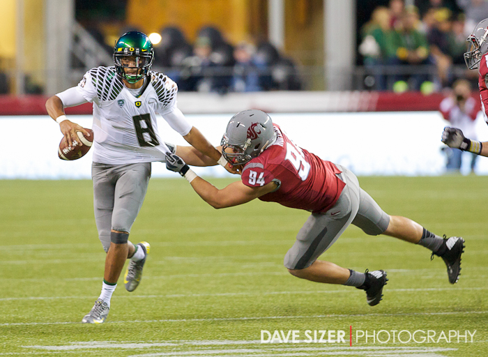 Oregon QB Marcus Mariota looks for a receiver as he tries to break free from Steven Hoffart.