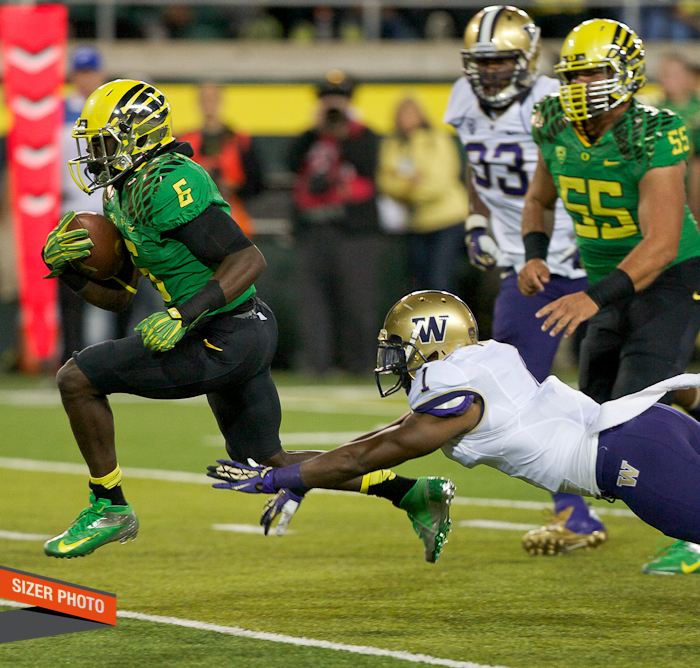 De'Anthony Thomas gets past Sammie Parker's dive on his way to a score.