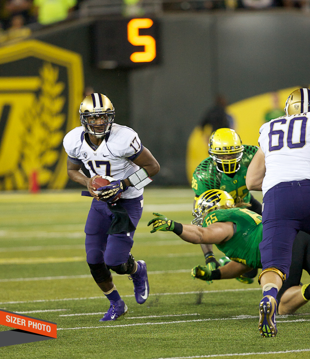 Huskies QB Keith Price scrambles away from the Duck defenders.