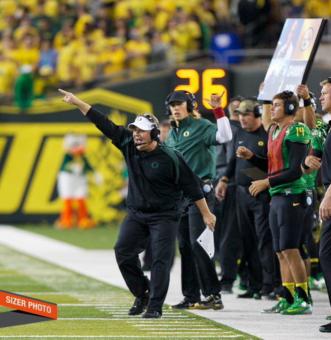 Oregon coach Chip Kelly tries to get a message in to his team.