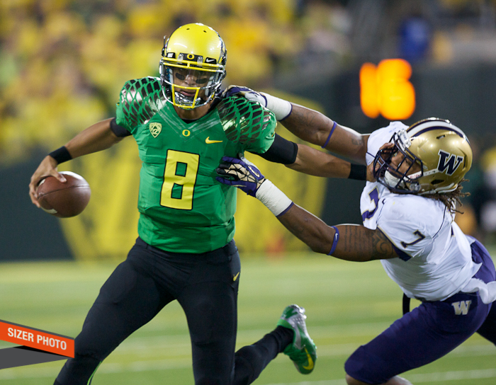 Ducks QB Marcus Mariota stiff arms Shaq Thompson on this run.