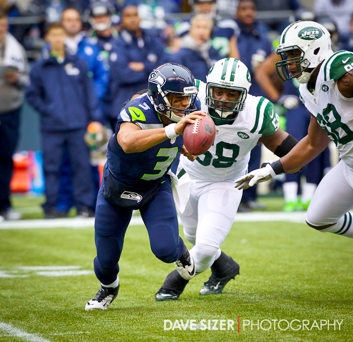 Russell Wilson scrambles away from the Jets defenders.