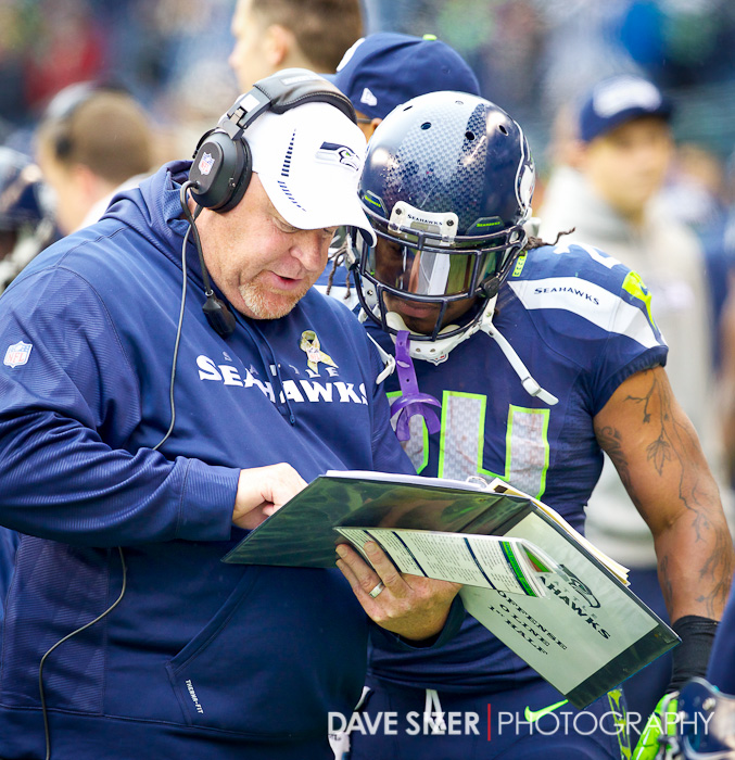 Lynch talks with O-Line Coach Tom Cable on the sideline.