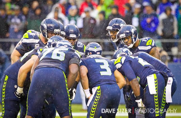 The offense huddles around Russell Wilson.