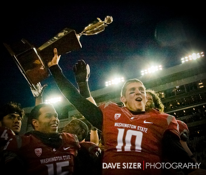 Senior QB Jeff Tuel raises the trophy high.