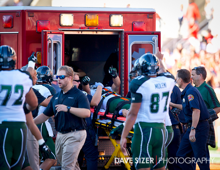 Brenden Daley waves to his teammates as he is loaded into an ambulance. Daley suffered a concussion in a collision.
