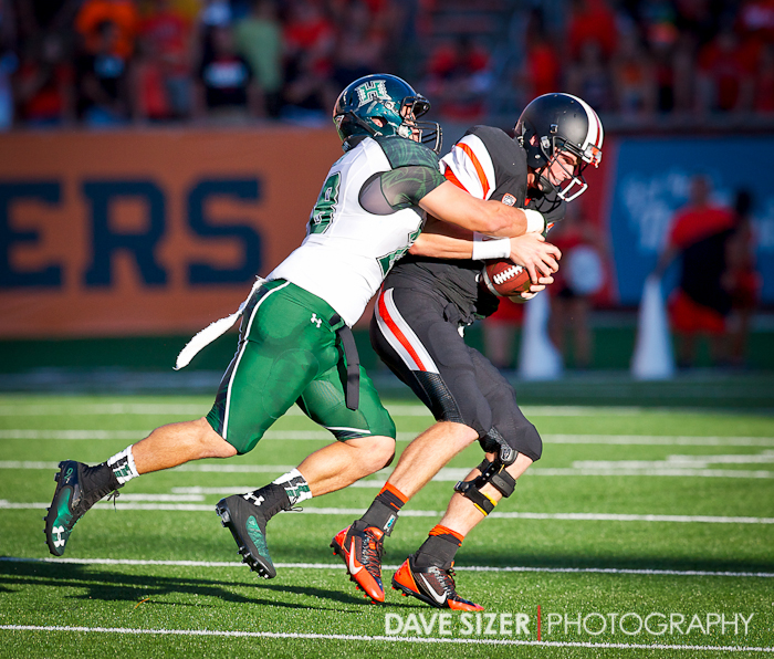 OSU Quarterback Sean Mannion gets sacked be a Warrior defender.