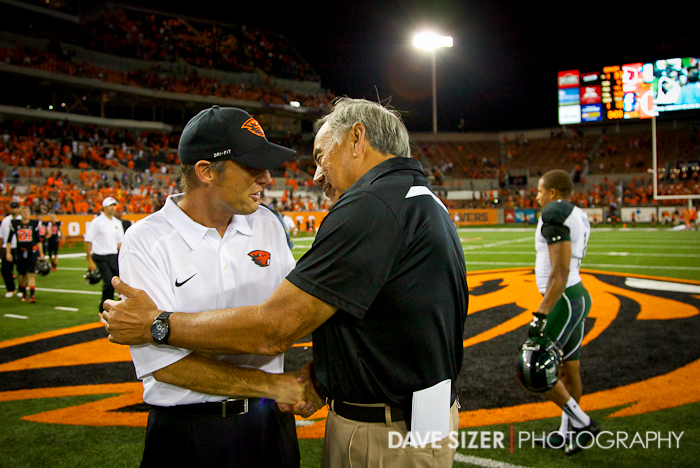 Head Coaches Norm Chow and Mike Riley shake hands at mid field after the game.
