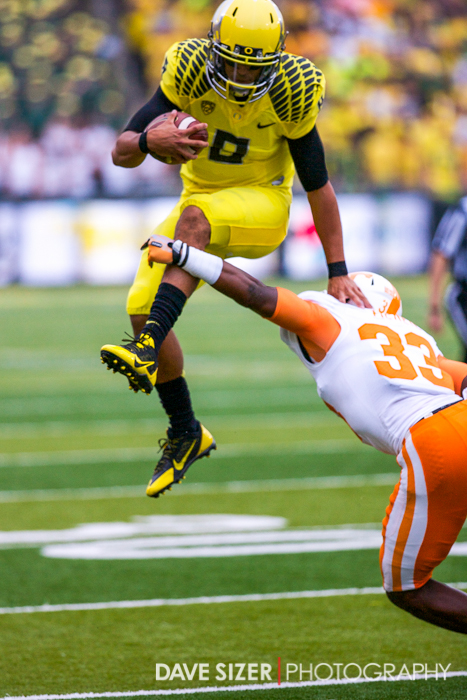 Oregon QB Marcus Mariota leaps to avoid the LaDarrell McNeil.