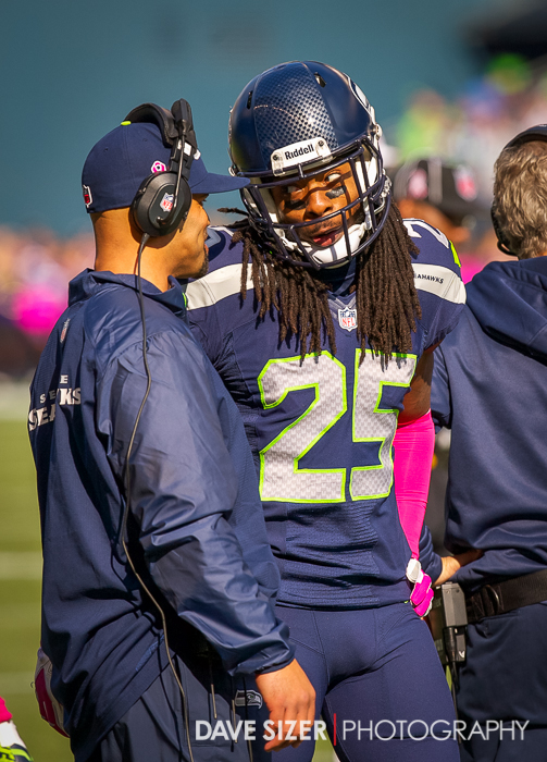Richard Sherman talking with one of his coaches.