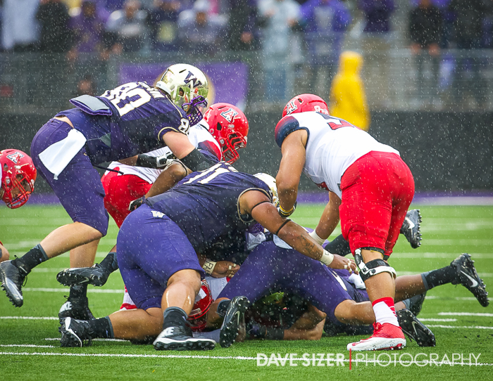 The Husky Defense swarms the runner.