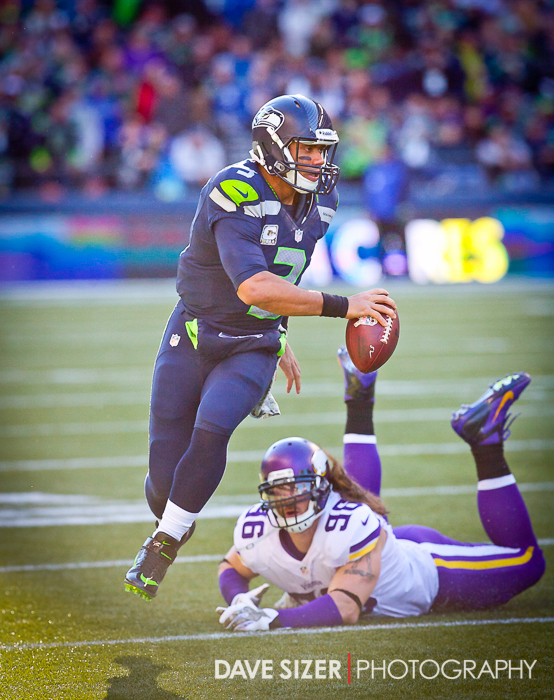 Russell Wilson eludes the rush from Brian Robinson.