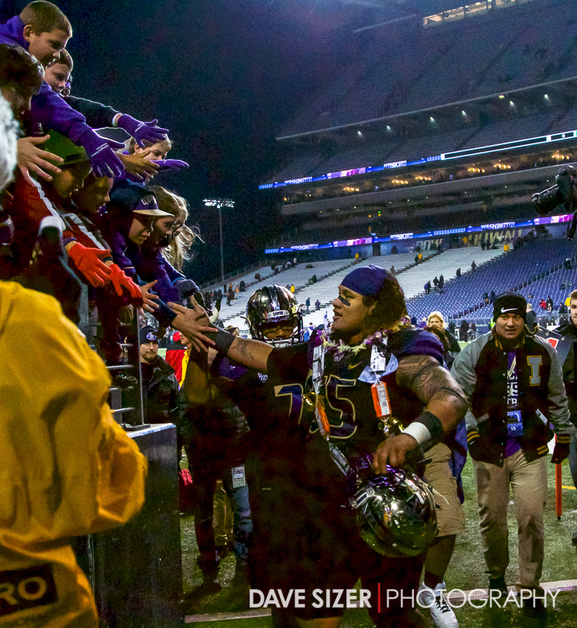 Danny Shelton shakes hands with the fans on the way off the field.