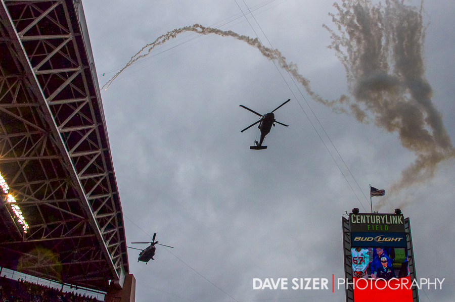 A couple of Military helicopters do a fly over during the pregame ceremonies.