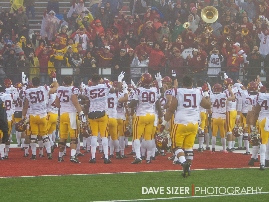 The Trojans sing the fight song with their fans in the corner of the stadium.