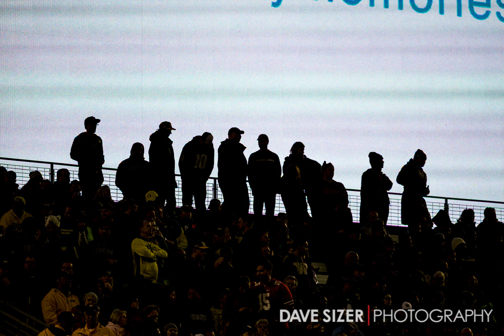 Fans in the last row of the end zone are silhouetted in front of the video board.