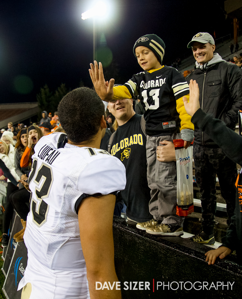 Colorado QB Sefo Lirufau makes this young fan's night by giving him a high five after the win.