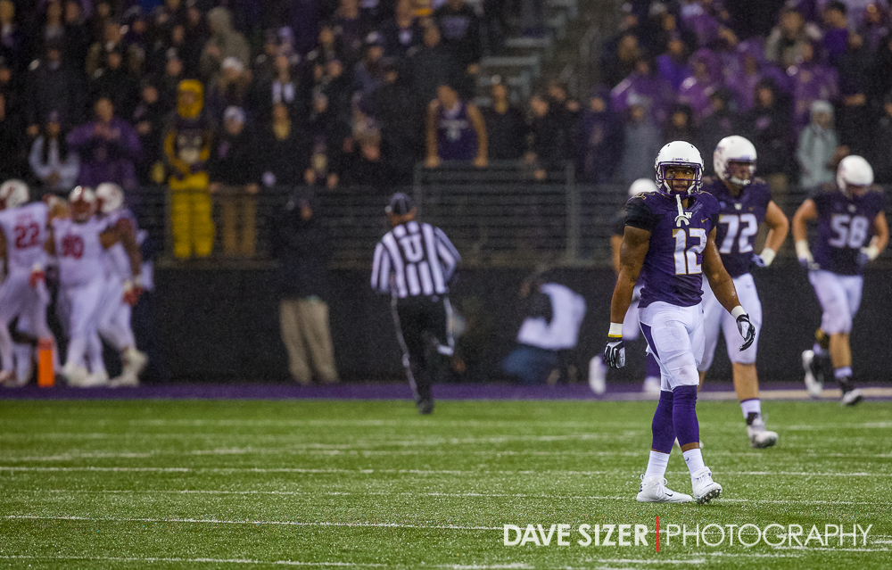 A dejected Dwayne Washington walks off the field after a fumble as the Utes celebrate the touchdown in the background.