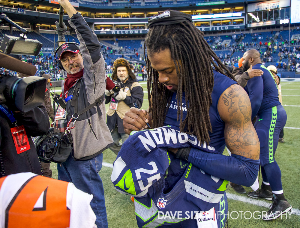 Richard Sherman signs a jersey for Johnson Bademosi