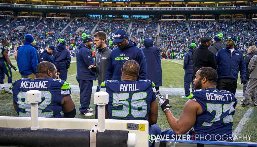 Brandon Mebane, Cliff Avril and Michael Bennett talk on the bench as the game winds down.