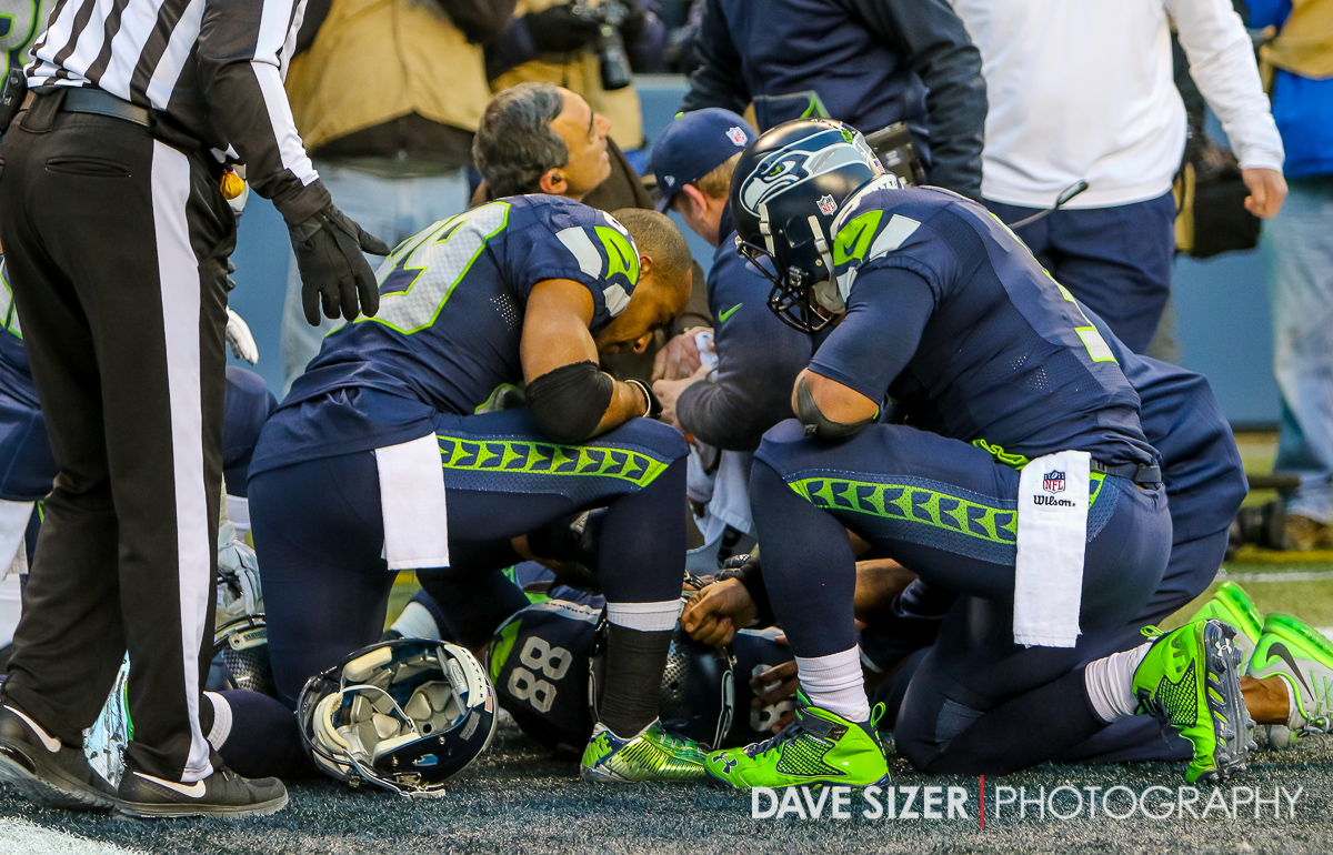 Doug Baldwin and Russell Wilson kneel by their fallen teammate.