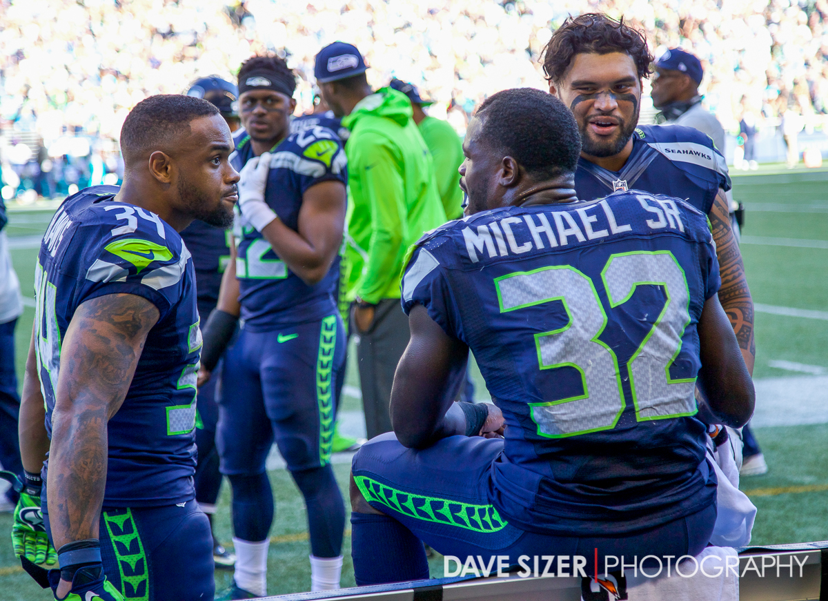 The running backs and full back talk on the bench.