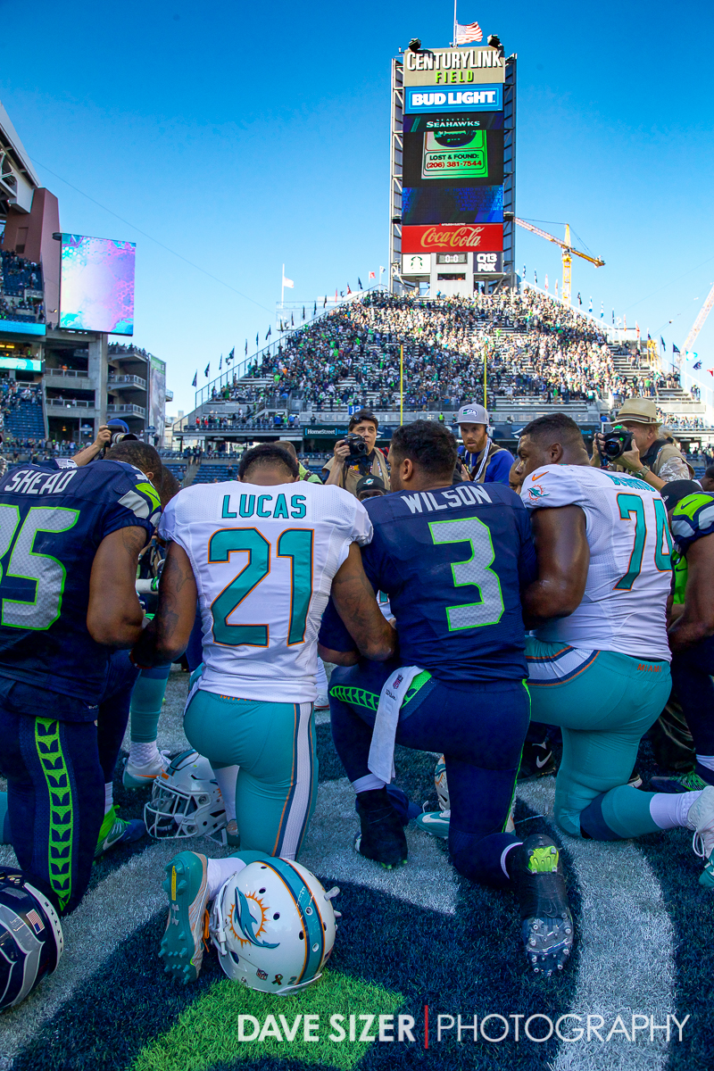 Players kneel down in prayer at midfield after the game.