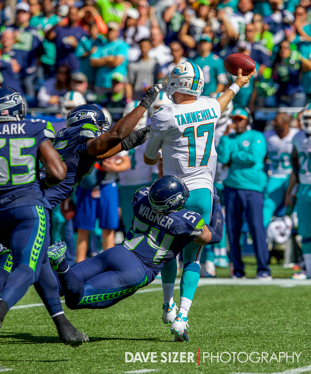 Bobby Wagner and Cliff Avril try to drag down Tannehill before he can get the pass off.