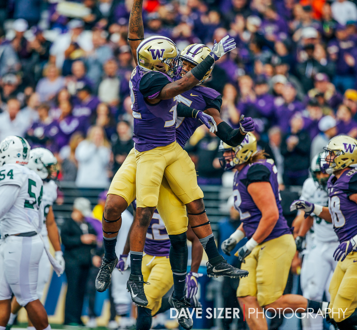Darrell Daniels and Budda Baker sky high in celebration after a touchdown.